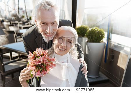 I am happy. Happy man embracing while standing behind his partner and holding flowers in right hand