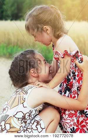 Two cute little girls smiling and playing at the field in warm sunny day