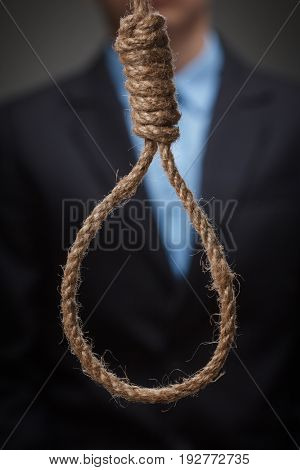 Desperate hopeless depressed young man is about to hang himself on the noose.