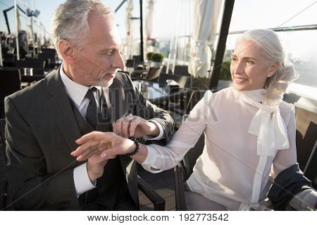 Give me your hand. Gallant male person sitting in semi position and pressing lips while talking with his partner