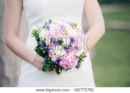 bride's hands hold a beautiful wedding bouquet