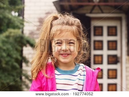 Portrait of a smillng adorable preschool girl at sunny summer day. Cute Girl Outdoors enjoying Summer Day. Happy kid.