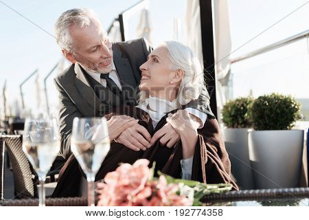 Tenderness in the air. Positive delighted blonde turning head to her cavalier and holding his hands while looking into his eyes