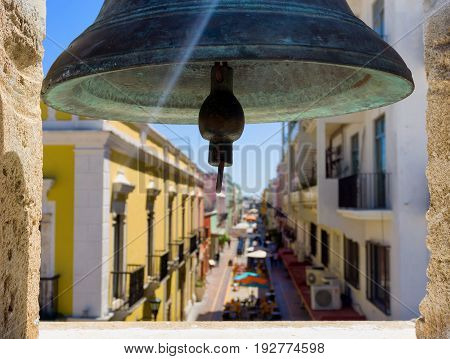 Bell in Campeche Mexico with the city out of focus in the background