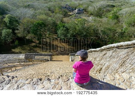 Tourist sitting on the pyramid looking down on the ruins of the ancient Mayan city of Ek Balam near Valladolid Mexico
