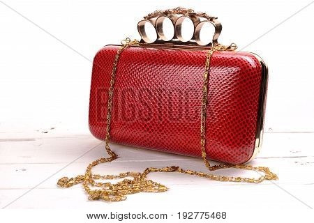 Red wallet purse with brass knuckles on white background.