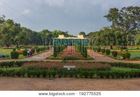Mysore India - October 26 2013: Grounds and green and red park of Tipu Sultan Summer Palace named Daria Daulat Bagh. Palace in back at end of visual lines. Green trees in back. Light blue sky.