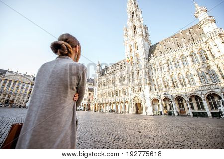 Young female tourist looking on the city hall standing at the Grand place in the old town of Brussels in Belgium