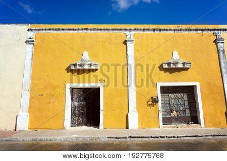 Facade of a historic yellow colonial building in Valladolid Mexico