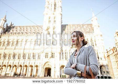 Young female tourist standing in front of the famous city hall in the center of Brussels in Belgium