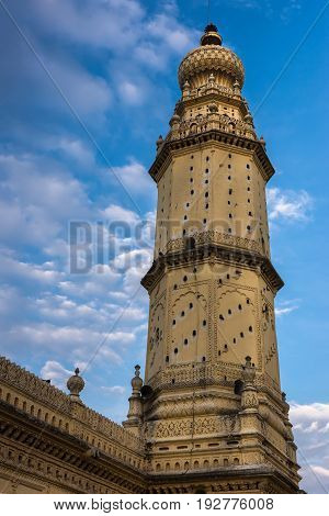 Mysore India - October 26 2013: Closup of yellow minaret and wall at Jamia Masjid mosque on Sriranagapatna Island. Doubles as pigeon housing. Blue cloudy sky. Shot from rampart.
