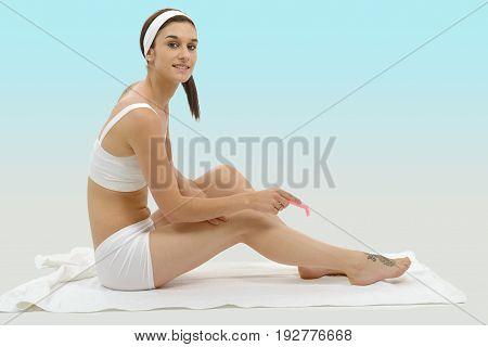 a beautiful adult caucasian woman shaving legs with razor