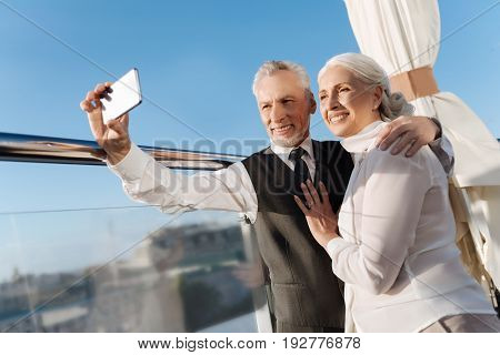 Time for photo. Handsome man holding telephone opposite himself while standing near his woman and looking together at camera