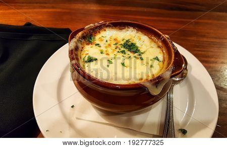 Delicious French Onion Soup in a crock with melted mozzarella cheese