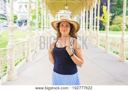 Young pretty woman is standing in the beautiful white colonnade in Karlovy Vary resort in Czech republic.
