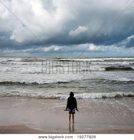 Man looking into stormy sea