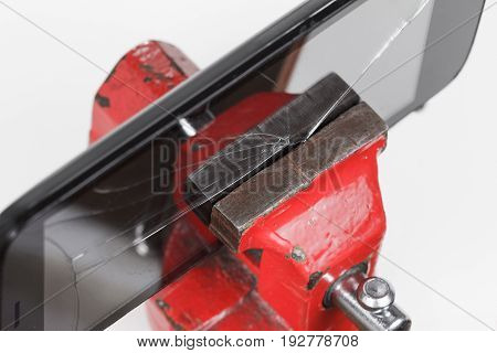 Concept. Close-up process of mobile phone repair with tools and vise
