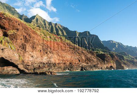 Kalalau trail path crosses steep ridge on Na Pali coastline in Kauai from sunset cruise
