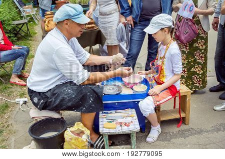 Zaporizhia/Ukraine- May 28, 2017: Charity Family festival:  Outdoors pottery workshop - ceramist master explaining to girl how to cut a piece of clay with a string. Art and craft activity.