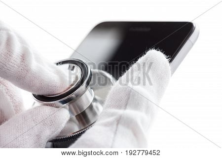Phone repair and service concept. Smartphone being diagnosed with a stethoscope. Isolated on white