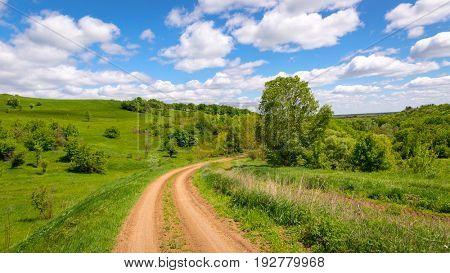Nice summer scene with rut road turn near green hills