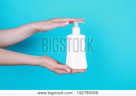 Female hands with bottle of cosmetic product for shower on color background