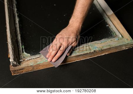 Hand of worker grinding surface of old window frame with abrasive paper, on dark background