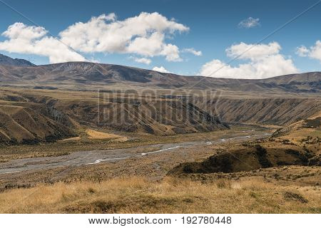 Middle Earth New Zealand - March 14 2017: High desert landscape with Lake Clearwater overflow drain to Rangitata River under blue sky with white clouds. Set in brown dry vegetation on mountains.