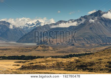Middle Earth New Zealand - March 14 2017: Meandering shallow Rangitata River among snow capped high mountains. Set in dry high desert scenery near Edoras under blue sky with white clouds.