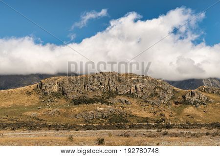 Middle Earth New Zealand - March 14 2017: Focus on the Rock of Middle Earth set in a high desert mountainous scenery under blue cloudy sky.