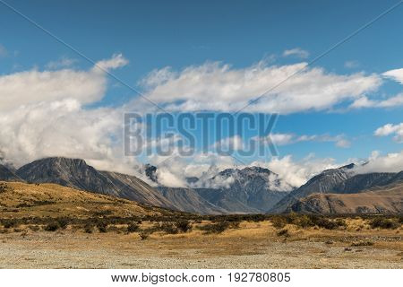 Middle Earth New Zealand - March 14 2017: Mountain range around the Rock of Middle Earth set in a high desert mountainous scenery under blue cloudy sky.