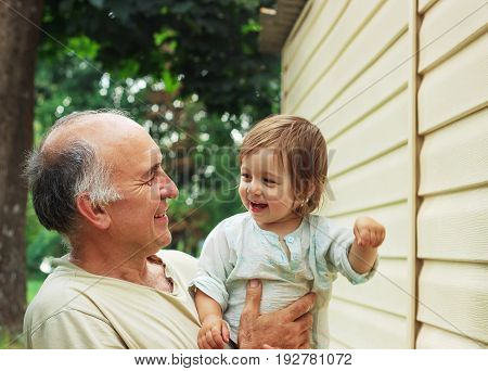 Portrait of Happy grandfather and grandaughter playing in the garden at Summer Day