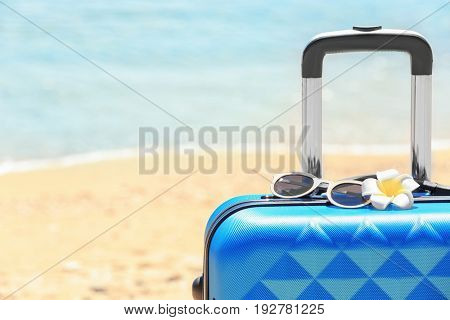Packed suitcase and sunglasses at sea shore, closeup. Vacation concept