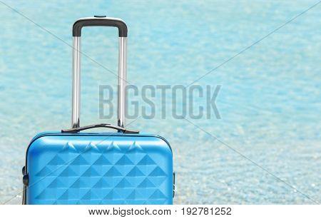 Packed suitcase and blurred sea on background. Vacation concept
