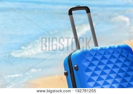 Packed suitcase and blurred sea on background, closeup. Vacation concept