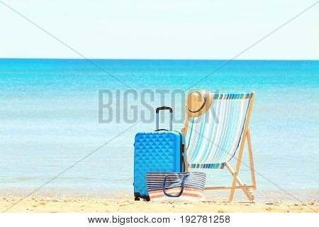 Packed suitcase, beach chair and accessories at sea shore. Vacation concept
