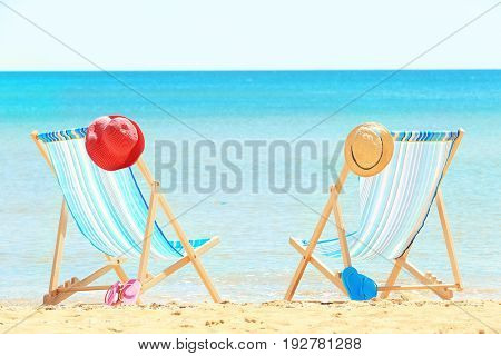Pair of beach chairs and accessories at sea shore. Vacation concept