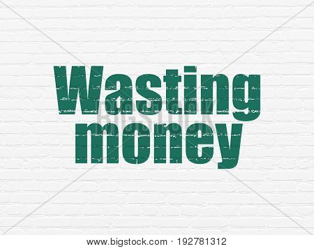 Banking concept: Painted green text Wasting Money on White Brick wall background
