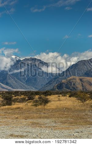Middle Earth New Zealand - March 14 2017: Portrait of Snow capped High mountain range around Rock of Middle Earth under blue sky with white clouds. Set in a high desert mountainous scenery.