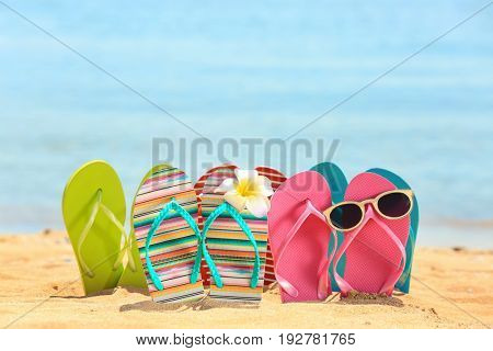 Colorful flip-flops, sunglasses and flower on sand at sea shore. Vacation concept