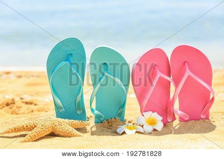 Colorful flip-flops and starfish on sand at sea shore. Vacation concept