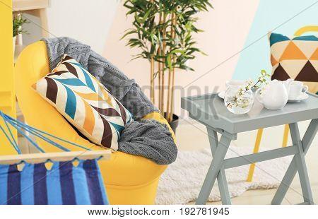 Cozy armchair and coffee table in beautiful veranda interior