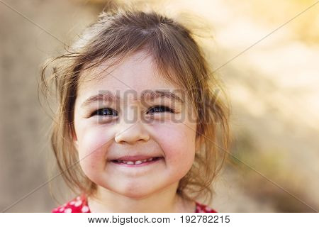 Portrait of a smilng adorable preschool girl at sunny summer day
