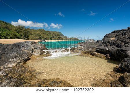 Rock pool frame the turquoise ocean off Lumahai Beach in Kauai in Hawaiian islands