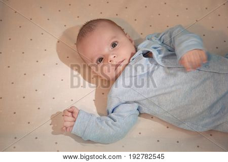 Cute little baby lying on bed at home. Sleep disorders concept