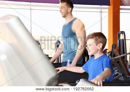 Dad training son on treadmill in gym
