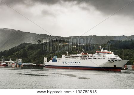 Picton New Zealand - March 12 2017: Interislander ferry leaves Picton port under heavy rainy skies. Green forest on mountains in back.