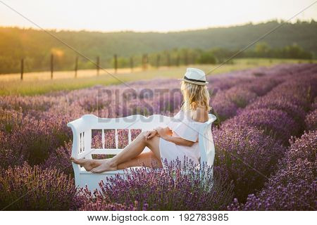 Romantic woman watching sunset at park bench. Lavender field at sunset.