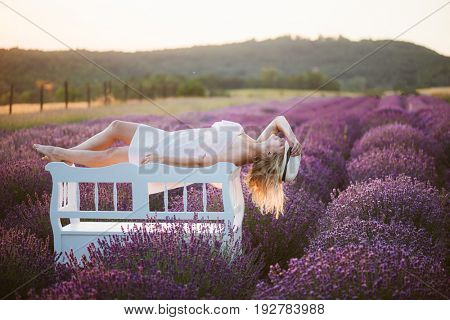 Young woman relaxing on beautiful vintage bench at lavender field at sunset.