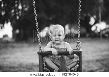 Happy child girl laughing and swinging on a swing at playground